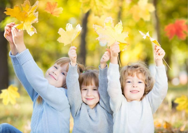 Bambini giocano con foglie secche
