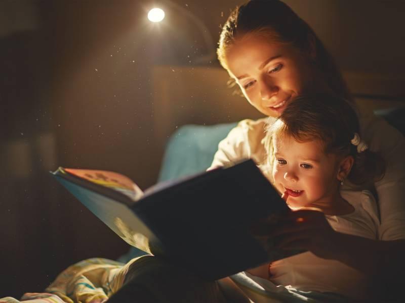mamma che legge nel lettino