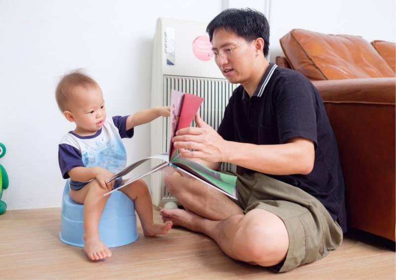 Papà legge il libro al bambino sul vasino