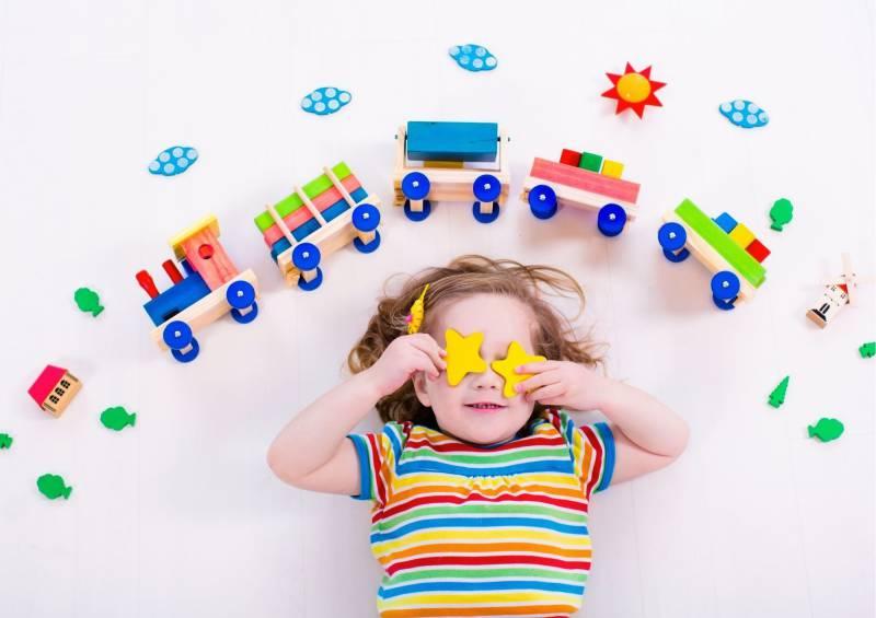 Bambina con trenino di legno