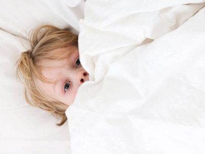 bambino sotto le lenzuola